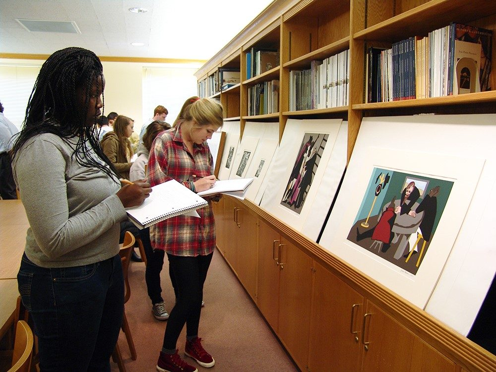 Students look at prints displayed in front of a bookcase and write in notebooks