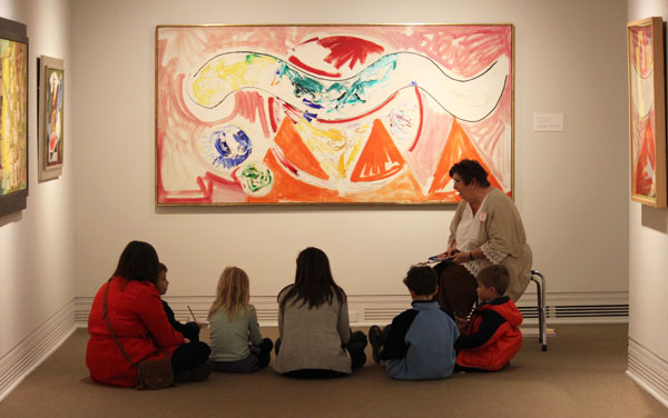 A group of kids listens to a docent in an art gallery