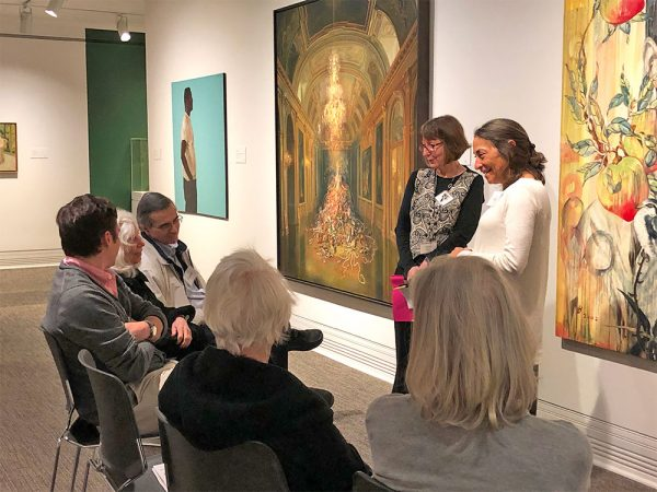 A group of people listens to a docent in an art gallery