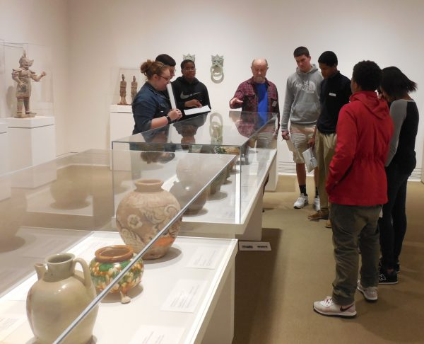 A group of people looks at art objects in a case