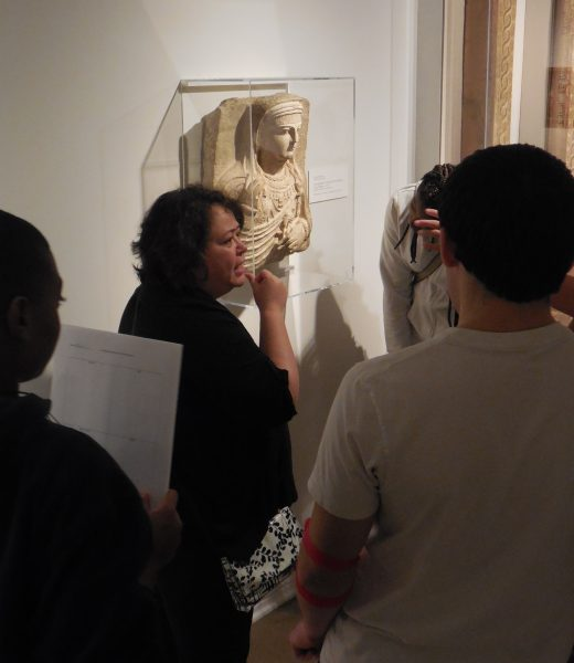 A group listens to a docent talking about a sculpture