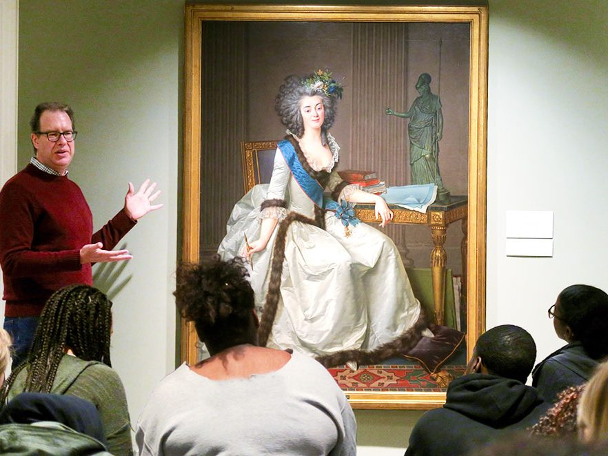 A professor gestures toward a painting of a woman while students look on