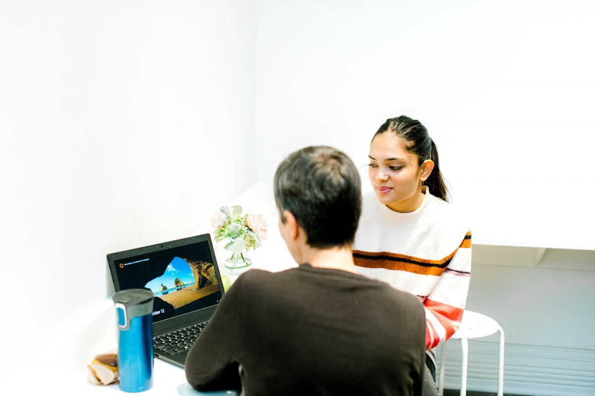 Two people look at a laptop together