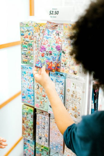close up photo of a hand touching a sheet of stickers in sticker display at the museum store