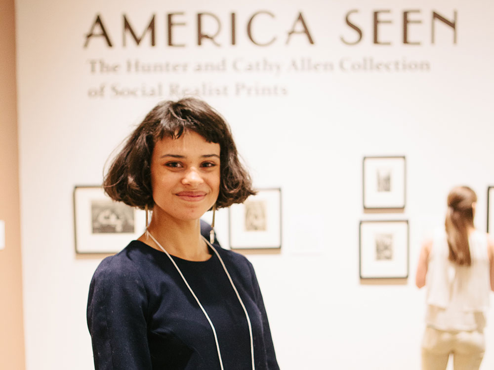 a woman with short hair stands smiling in a museum gallery with America Seen written on the wall behind her