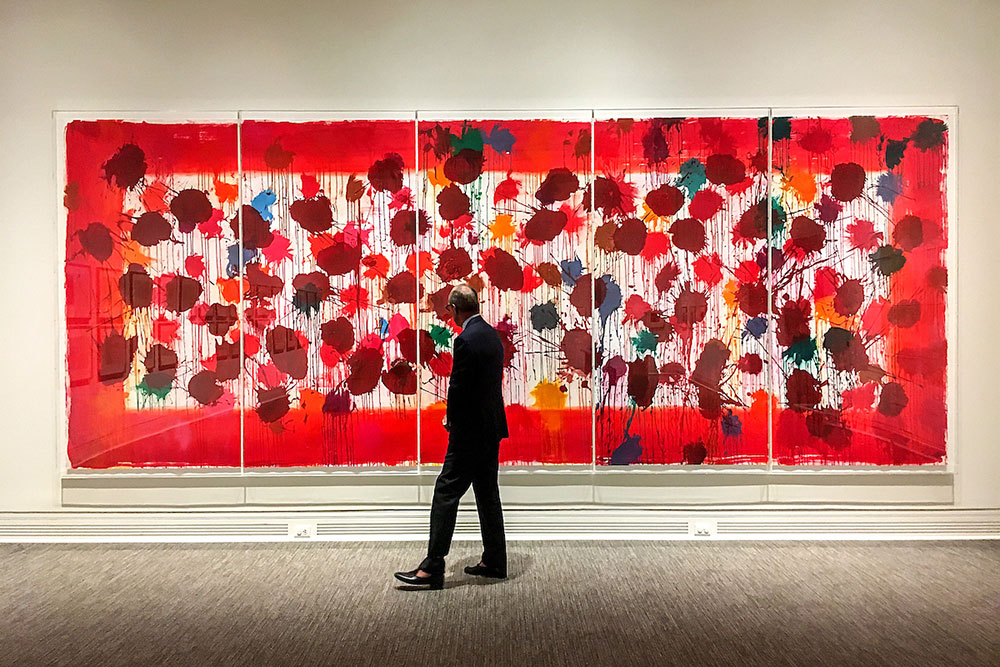 A man walks in front of a large red painting