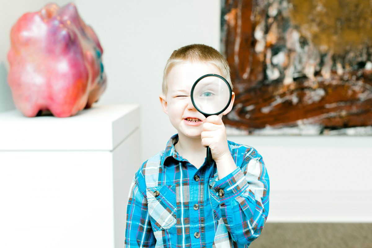 little boy looks at the camera through a magnifying glass