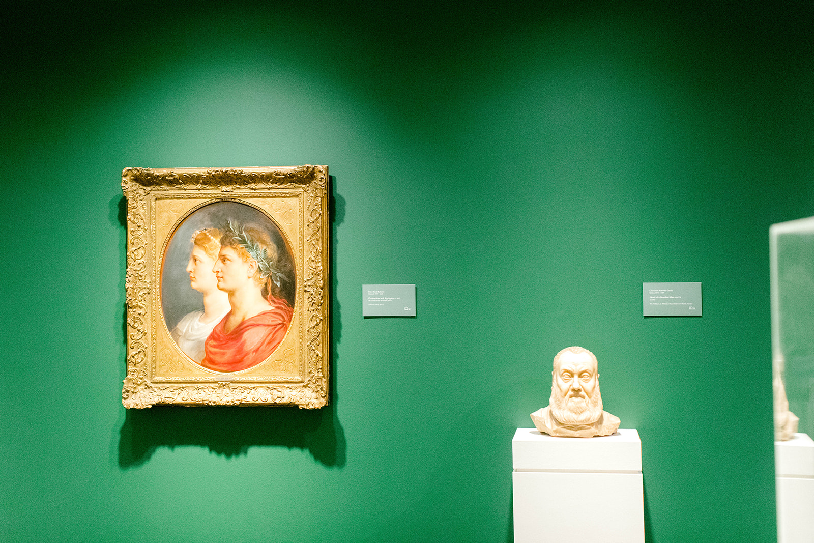 A painting of two people in profile and a marble bust of a man's head on view in an art gallery
