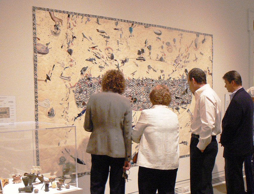 Three people look at a large collage