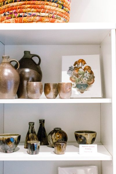photo of museum store display showing pottery and a print