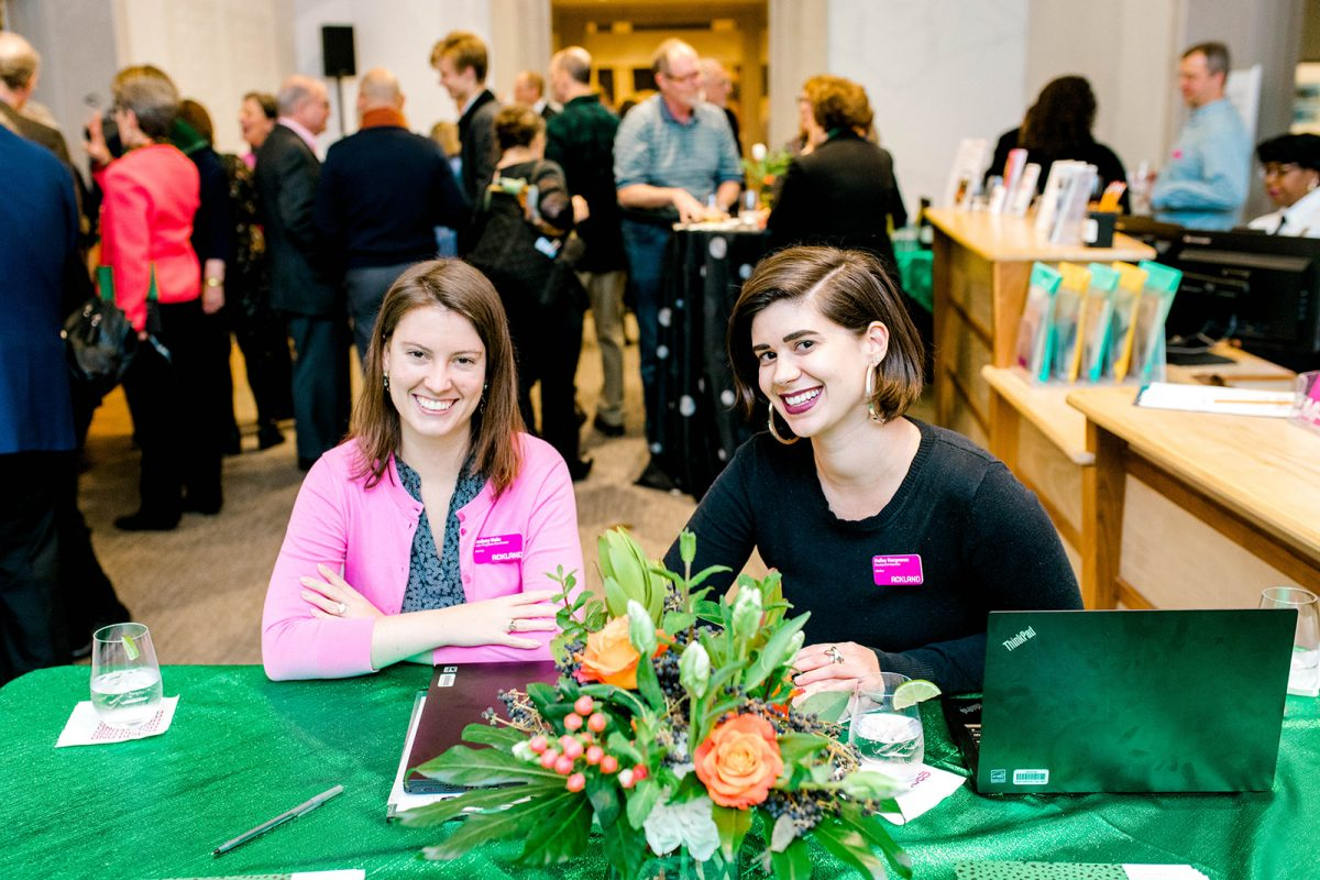 two people sit smiling at an event registration table