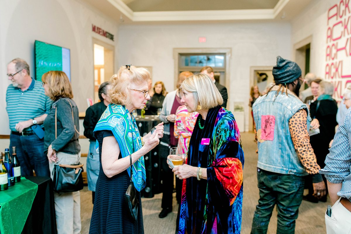 Two women lean in to have a conversation in a crowded museum lobby