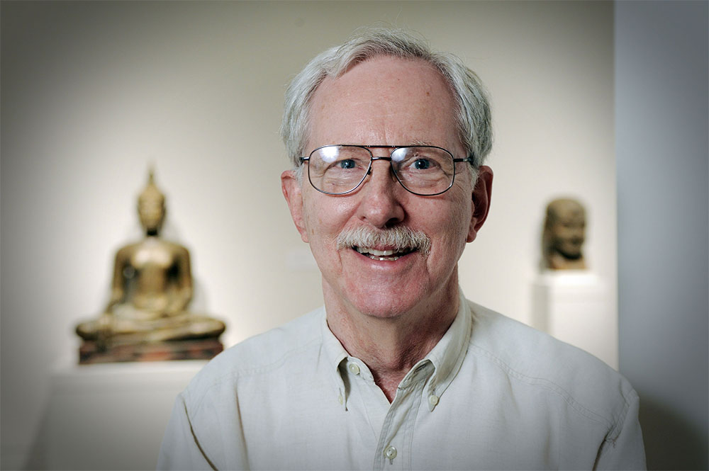 Head shot of Charles Millard smiling in front of a Buddha statue