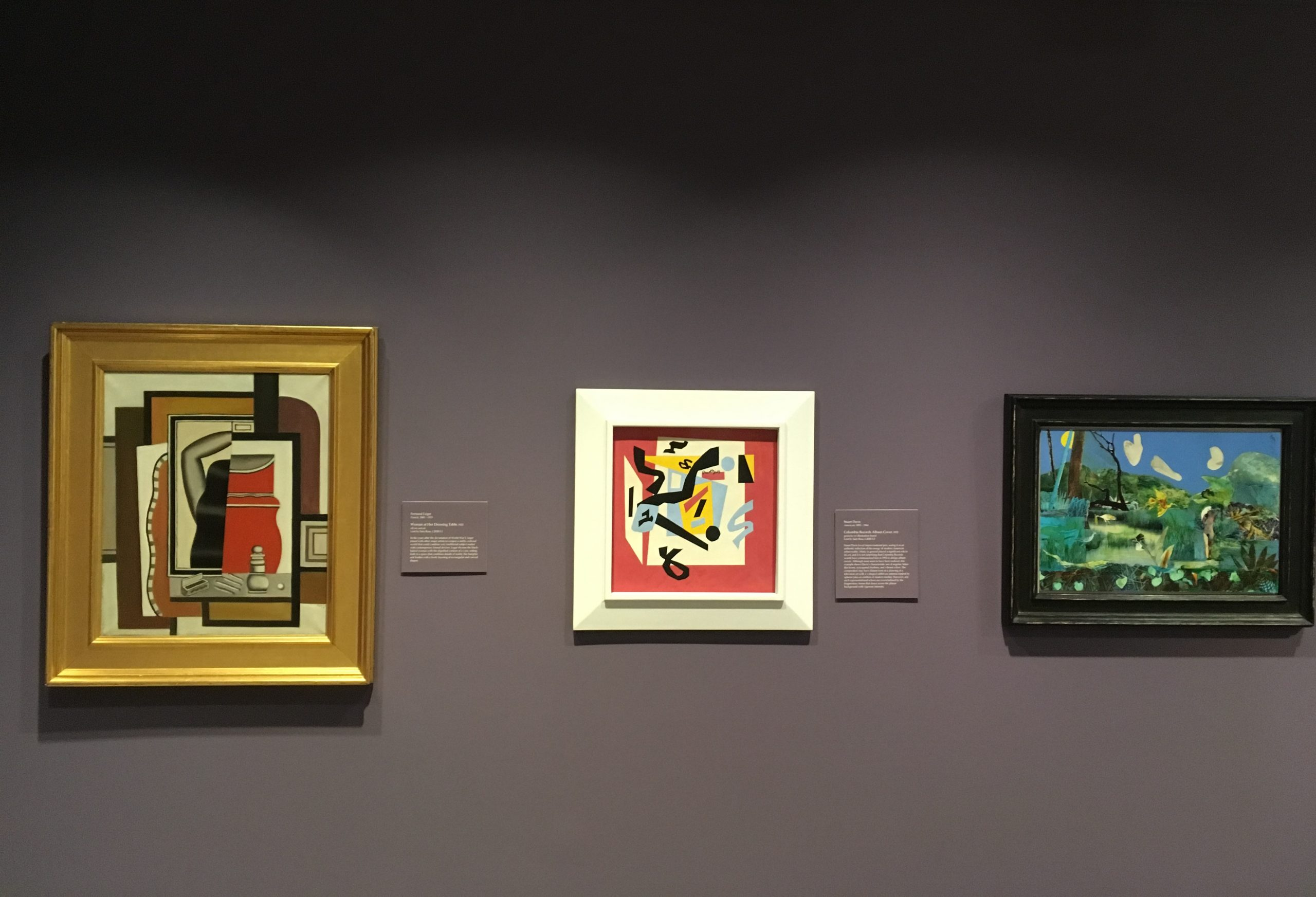 Three framed abstract paintings hanging on a purple wall in the Ackland Art Museum