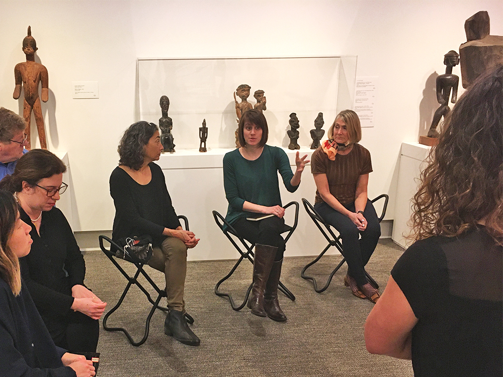 A group of people sit on stools talking in an art gallery with African objects