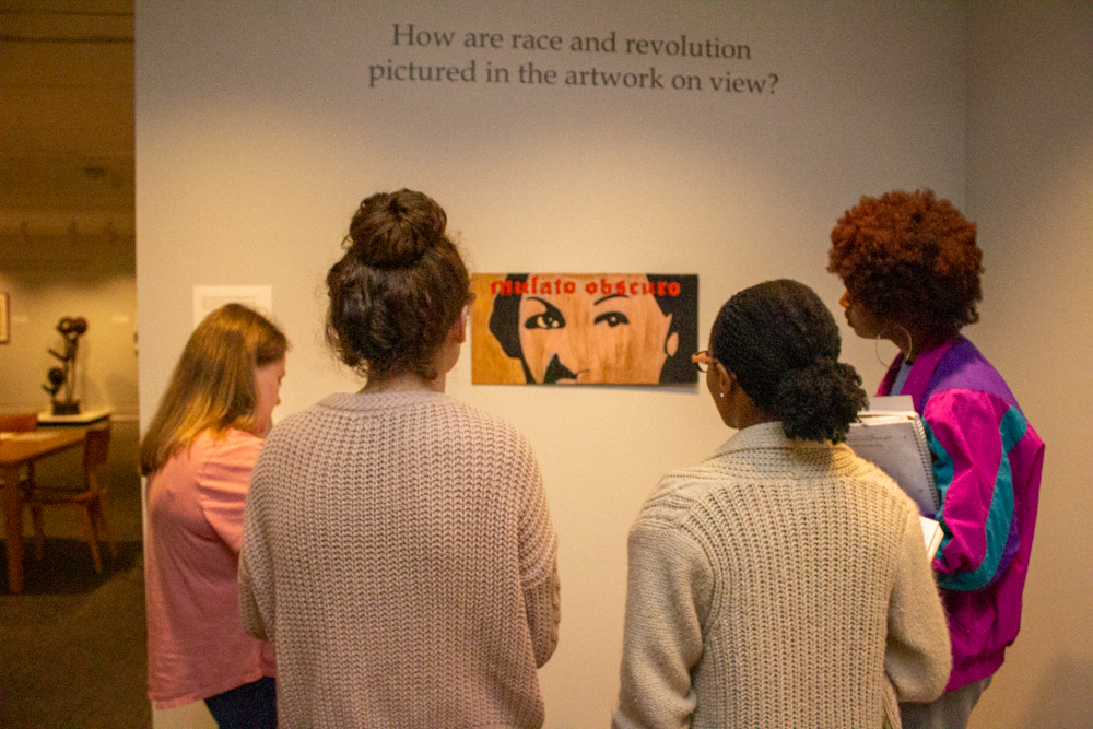 four people look at a painting of a person's eyes. A question on the wall reads How are race and revolution pictured in the artwork on view?