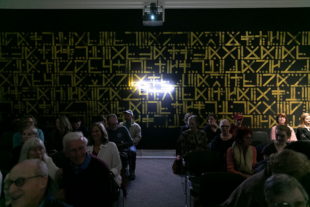 an audience sits in a dark room with a neon sign glowing on the back wall against a mural of gold heiroglyphics