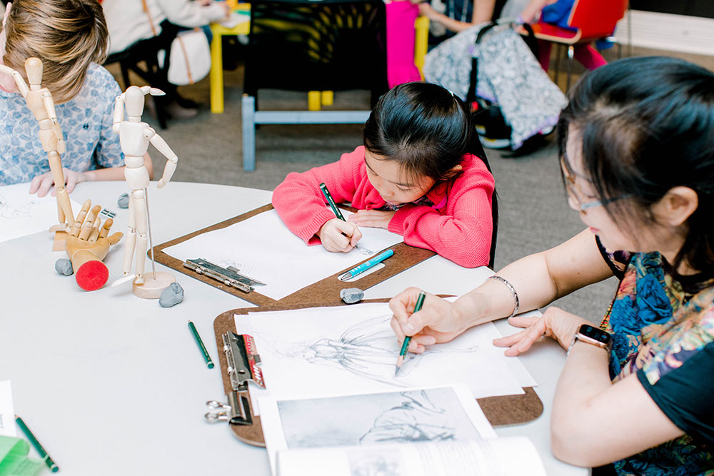 a mother and daughter sit at a table drawing with books and wooden models in front of them - a great art activity to do at home during the coronavirus quarantine!