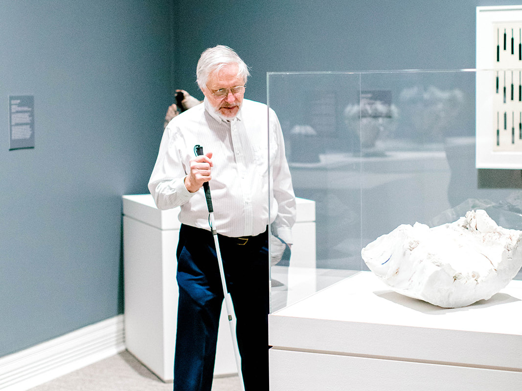 a man with low vision carrying a white cane looks at a sculpture in a display case