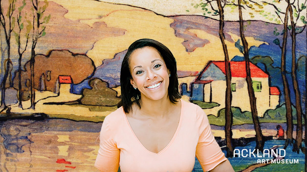 a woman smiles while sitting in front of a digital background showing a landscape painting with the Ackland Art Museum logo in the corner