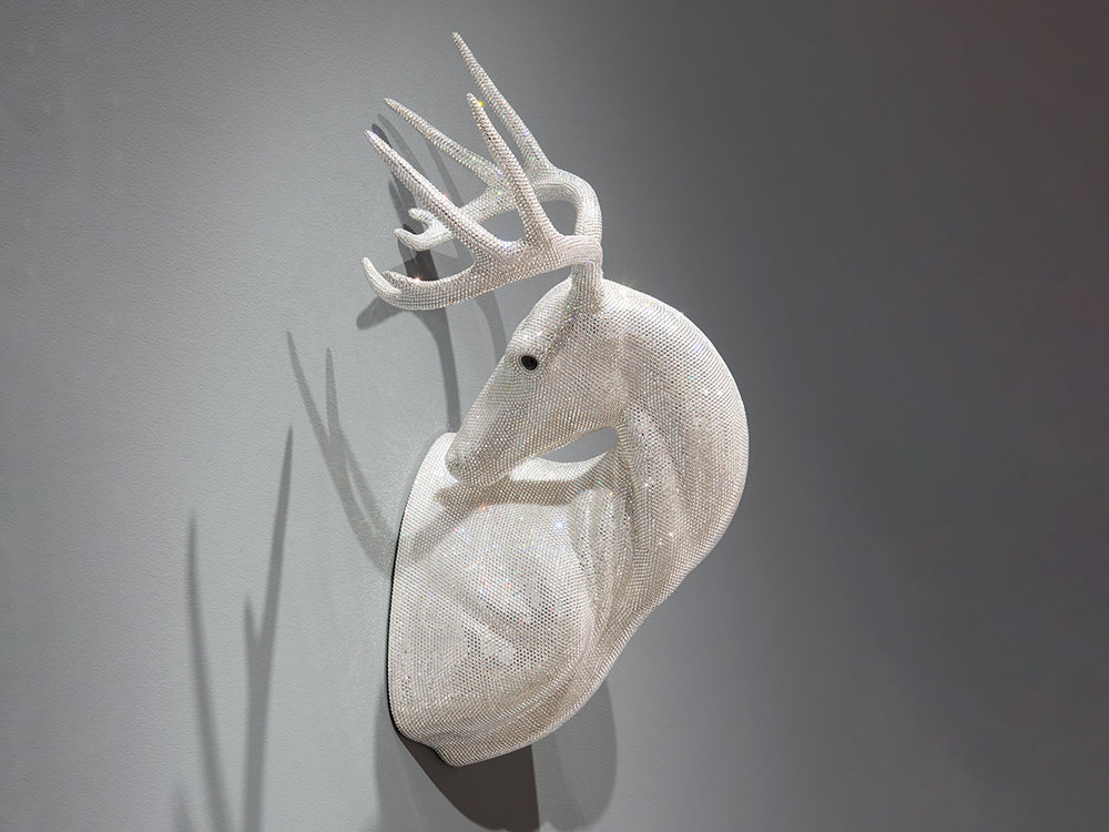 sculpture of a buck's head looking back, covered in crystals