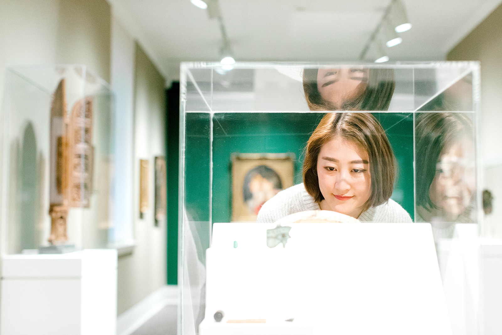 A woman looks at a work of art in a glass case