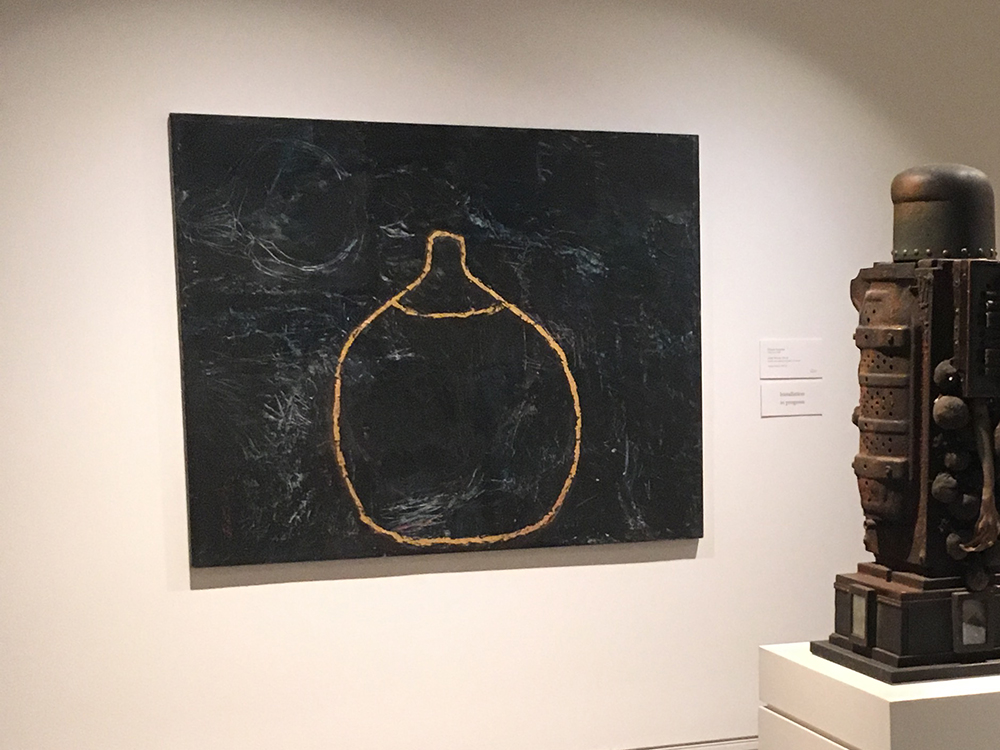Painting of the outline of a breast in gold on a black background hanging on a wall behind a sculpture on a pedestal
