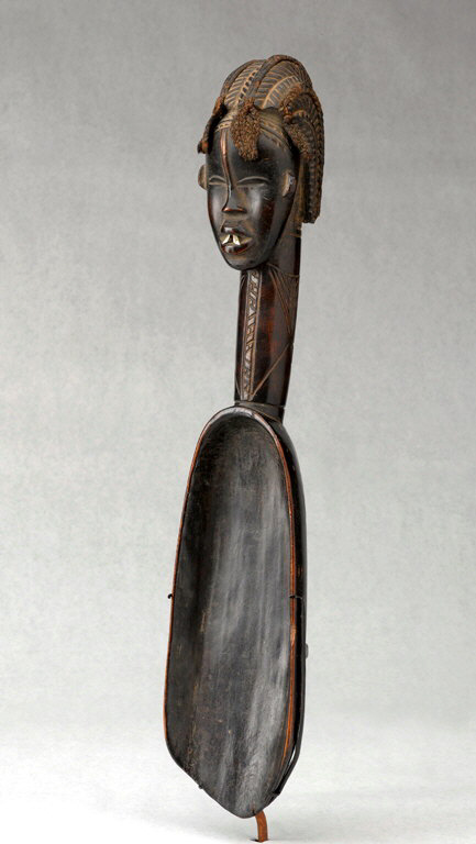 A carved wooden spoon with handle in shape of a human head
