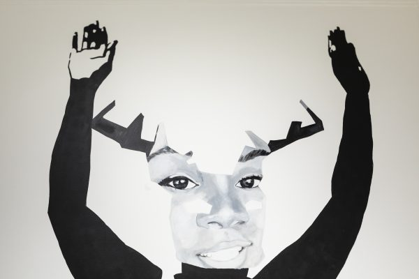 A grayscale painting of Breonna Taylor smiling with her hands raised in the air and antlers growing from her head