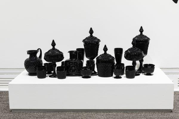 A white platform holding about a dozen black glass vessels
