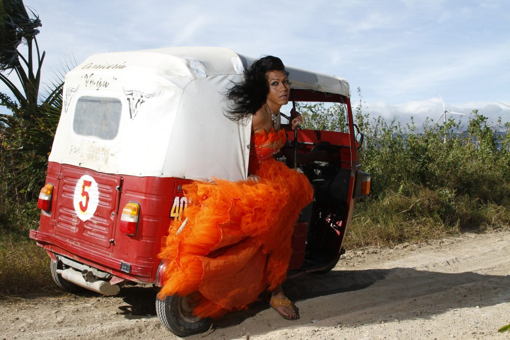 person with long flowing black hair and a long billowing orange dress looks back out of a mototaxi