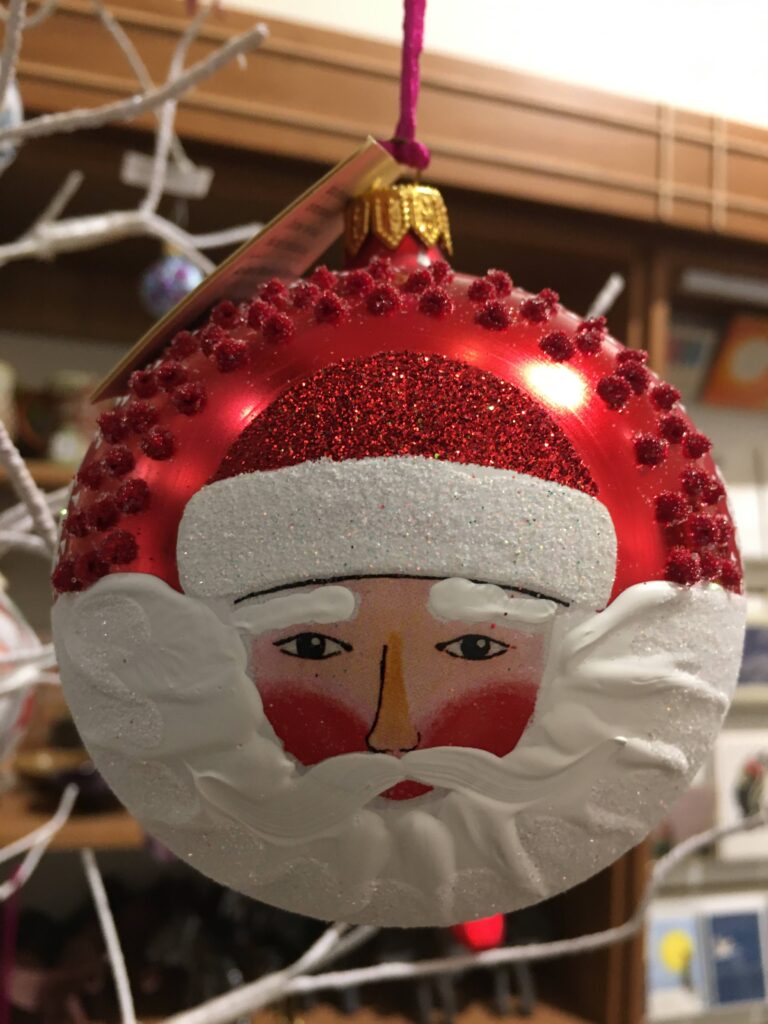 Christmas tree ornament made of red glass with a painting of a pink-faced man with a flowing white beard