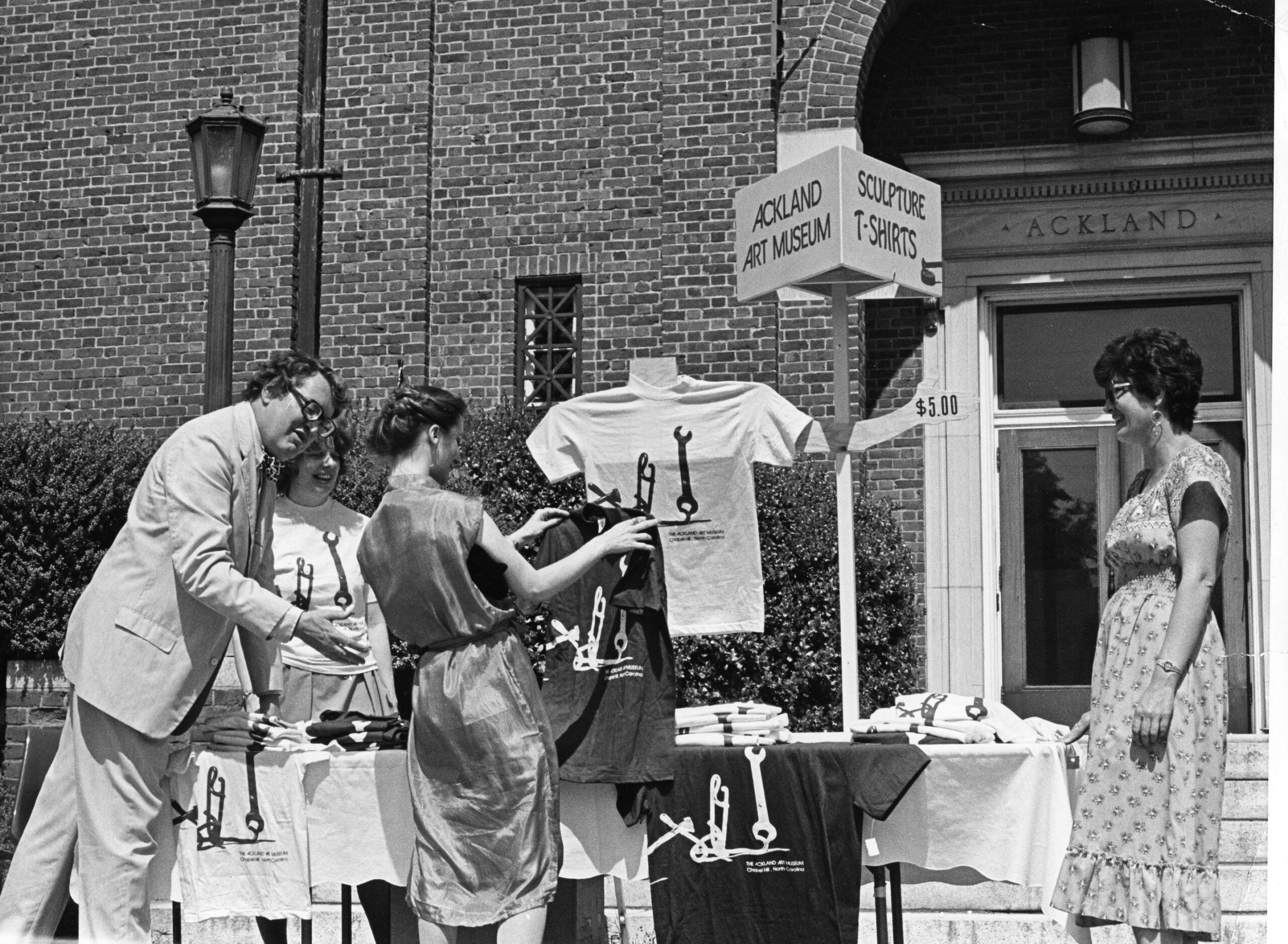A group of four people looking at t-shirts on a table outdoors