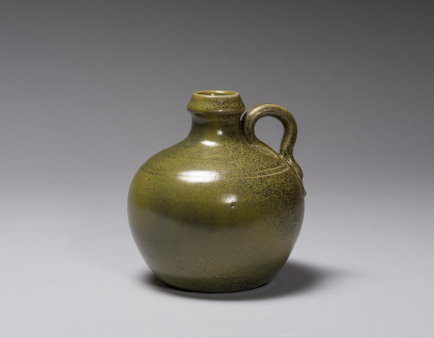 A short glossy greenish jug with a small round handle and a cork in the opening
