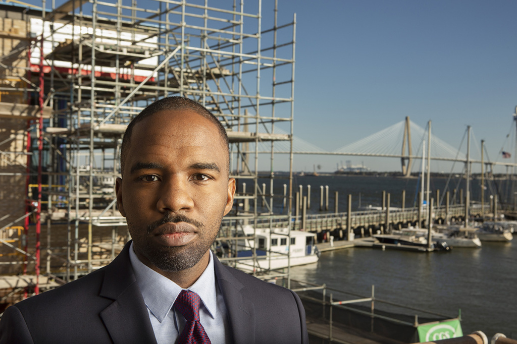 A man in a jacket and tie stands in front of a construction site
