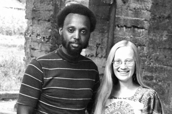 A black and white photo of a man in a striped t-shirt with dark skin and short dark hair and a woman in a square-neck top with light hair, light skin, and glasses