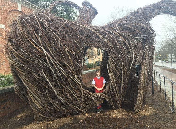 A child stands inside a giant stickwork sculpture