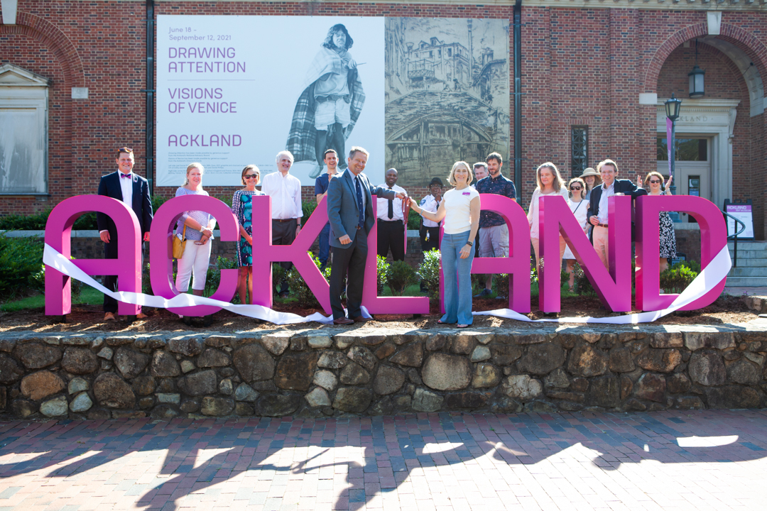 A group of people stand around a magenta sign as two people cut a ribbon draped around the sign
