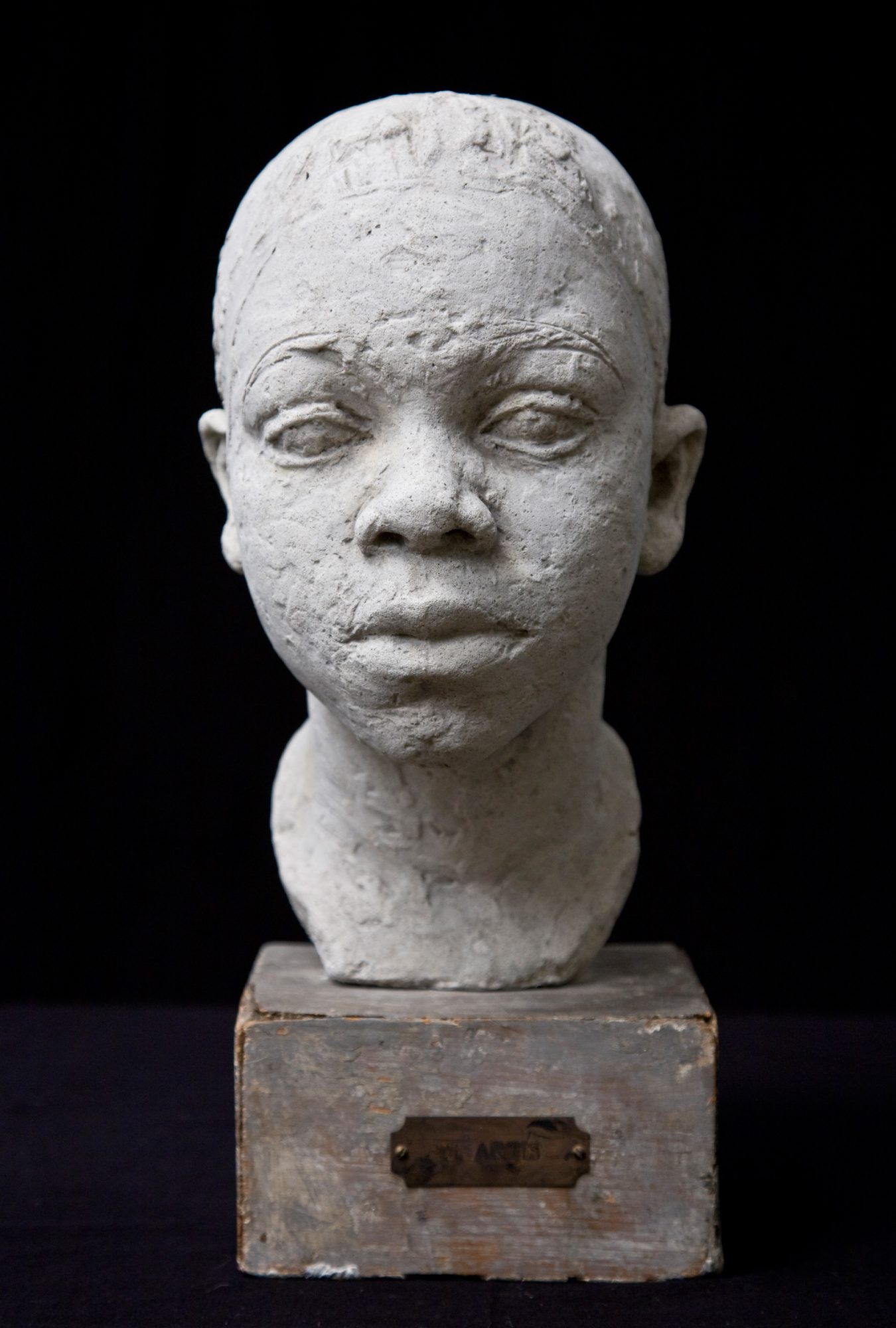 Low-fired clay sculpture of a head of a boy mounted on a wood pedestal