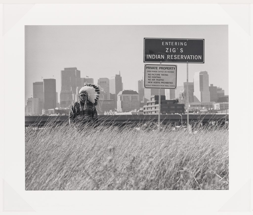 """A black and white photograph that shows Zig Jackson, the artist, in a half-length portrait, standing, facing front and wearing a headdress, sunglasses, and a plaid shirt. Zig stands next to a large sign in the style of a city or landmark sign with a dark background and white lettering that states """"Entering Zig's Indian Reservation."""" Below is a smaller white sign with black lettering that states: """"Private Property, open range cattle on highway, No Picture Taking, No Hunting, No Air Traffic, New Agers Prohibited, without permission from Tribal Council."""" Zig stands in tall grass with a highway and a cityscape of San Francisco, California behind him."""